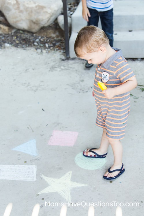 Fun toddler activity to help improve gross motor skills - jumping on colored chalk shapes - Moms Have Questions Too
