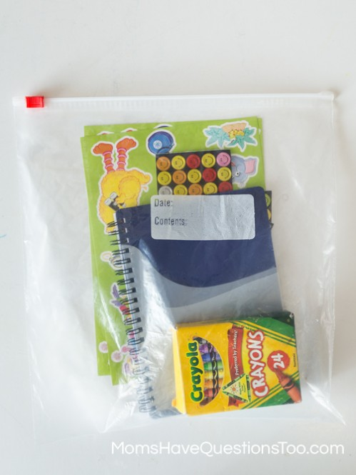 Contents of a simple busy bag for toddlers with paper stickers and crayons - Moms Have Questions Too