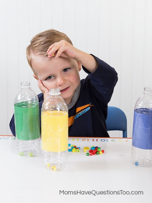 Toddler activity - putting beads in a waterbottle - Moms Have Questions Too