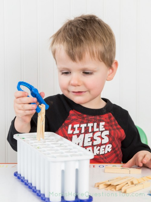 Pick up clothes pins with kid tweezer and drop into an ice cube tray - Moms Have Questions Too