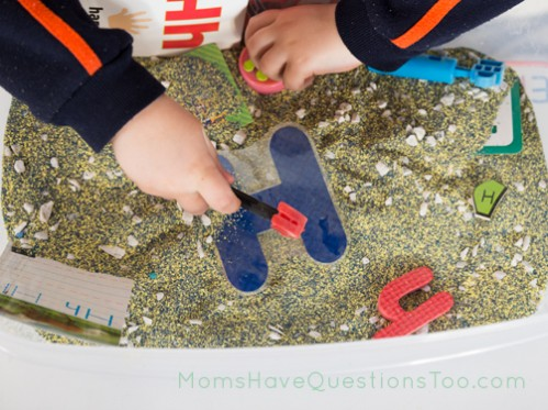 H sensory bin. The base is colored sand and a few aquarium rocks. Lots of uppercase and lowercase Hs, plus a hammer, a hat and more.